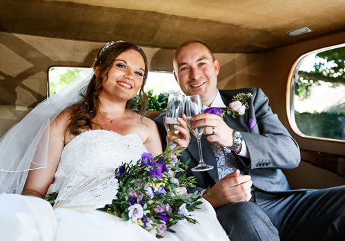 Wedding bride and groom celebrate with champagne in our vintage cars